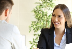 Male job candidate shaking hands with female employer at a job interview